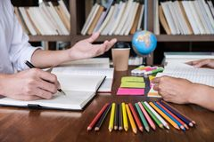 Tutor books with friends, Young students campus or classmates helps friend catching up workbook and learning tutoring in classroom royalty free stock photos