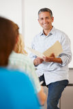 Tutor with class of students. Tutor sitting in front of class of students Royalty Free Stock Image