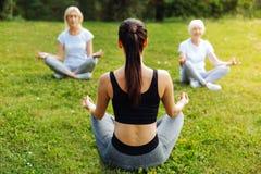 Tutor concentrado que senta-se na pose da ioga Imagens de Stock Royalty Free