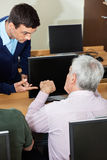 Tutor Discussing With Senior Man In Computer Class. High angle view of male tutor discussing with senior men at desk in computer class Royalty Free Stock Photos