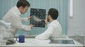Tutor doctor help intern with x-ray stock video