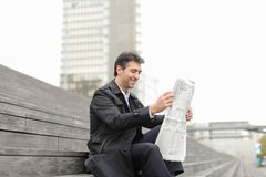 Male business tutor sitting on stairs and reading newspaper. Tutor dressed in gray coat sitting on rung and read morning newspaper. Articles pleased man and Royalty Free Stock Image