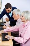 Tutor Explaining Senior Students Using Computers In Classroom Stock Photo