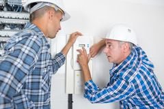 Tutor explaining thermostat to students. Thermostat royalty free stock photo