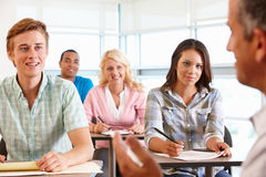 Tutor in front of class. Of students smiling and laughing Stock Photo
