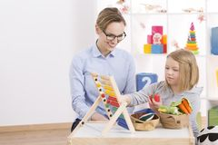 Tutor and girl counting with abacus Stock Photos