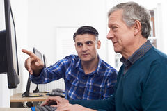 Tutor Helping Mature Man In Computer Class Royalty Free Stock Images