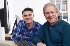 Tutor Helping Mature Man In Computer Class Stock Photo