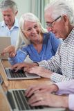 Tutor Helping Senior Man In Computer Class royalty free stock images