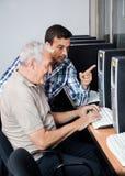 Tutor Helping Senior Man In Using Computer. Male tutor helping senior men in using computer at classroom Royalty Free Stock Images