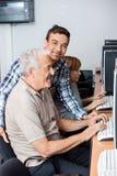 Tutor Helping Senior Man In Using Computer. Male tutor helping senior men in using computer at classroom Royalty Free Stock Photos