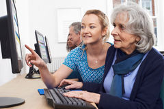 Tutor Helping Senior Woman In Computer Class. Tutor Helps Senior Woman In Computer Class Stock Photo
