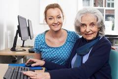 Tutor Helping Senior Woman In Computer Class. Tutor Helps Senior Woman In Computer Class Stock Photography
