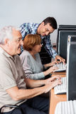 Tutor Helping Senior Woman In Using Computer. Male tutor helping senior women in using computer at classroom Royalty Free Stock Image
