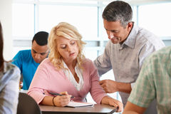 Tutor helping student during class Royalty Free Stock Photo