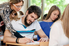 Tutor helping student in class Royalty Free Stock Images