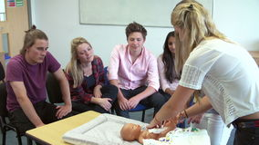 Tutor Helping Students On Childcare Course To Change Diaper. Tutor instructing college students in childcare class how to change nappy.Shot on Sony FS700 at stock footage