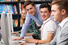 Tutor Helping Teenage Students Wotking At Computers Royalty Free Stock Photography