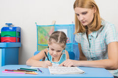 Tutor helps the child to spell the alphabet Stock Photography