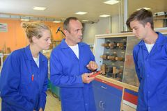 Tutor holding equipment and talking to apprentice stock images
