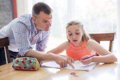 Tutor home masculino Helping Teenage Girl com estudos fotografia de stock royalty free