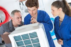Tutor instructing trainee electricians. 2 Royalty Free Stock Photos