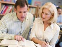 Tutor la ayuda del estudiante maduro en biblioteca Foto de archivo libre de regalías