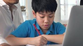 Tutor les enfants de pièce dans la classe apprenant sur l'ordinateur portable avec le professeur banque de vidéos