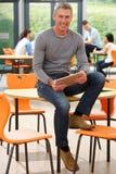 Tutor masculino Sitting In Classroom com tabuleta de Digitas imagem de stock