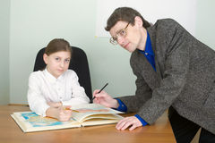Tutor and schoolgirl with atlas Royalty Free Stock Photo