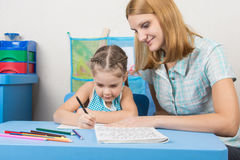 Tutor sees that the child turns out to write letters of the alphabet Stock Photo