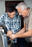 Tutor And Senior Man Fixing Computer In Class. Male tutor and senior men fixing computer in classroom Royalty Free Stock Photo