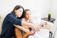 Tutor Showing Musical Notes To Girl Playing Guitar. Female tutor showing musical notes to girl playing guitar at home royalty free stock image