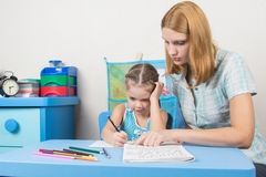 Tutor teaches the child to write letters Stock Photography