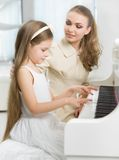 Tutor teaches little child to play piano. Master teaches little girl to play piano. Concept of music study and arts Royalty Free Stock Photos