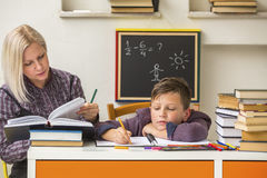 Tutor teaches a school Boy with his studies. Help. Tutor teaches a school Boy with his studies stock photography