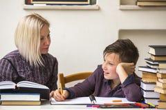 Tutor unterrichtet einen jungen Studenten mit seinen Studien Ausbildung Lizenzfreie Stockfotos