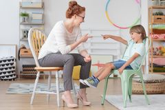 Tutor working with little boy. Professional female tutor having fun playing and working with little boy during private lesson at home Royalty Free Stock Photos