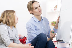 Tutor writing on whiteboard. Private tutor writing on whiteboard and little girl listening Royalty Free Stock Images