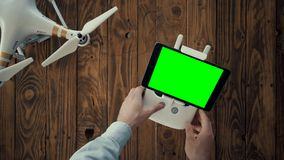 Tutorial of drone control. Top view,hands put remote controller on wooden table, mount small black tablet with chromakey screen and turn on drone in left corner stock footage