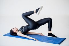 Tutorials for cardio beginners. The attractive sportive brunette is doing crab kicks while lying on the exercise mat in. The white studio Stock Images