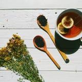 tutsan e tazza di tè con il limone, tè all'ingrosso su un cucchiaio di legno del fondo bianco Immagini Stock
