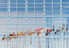 Tutte le bandiere di Unione Europea hanno riflesso nella facciata del Parlamento Europeo Immagini Stock