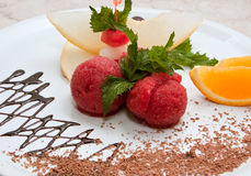 Tutti-frutti. Colored ice cream with fruit on a white plate with chocolate Stock Photos