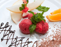 Tutti-frutti. Colored ice cream with fruit on a white plate with chocolate Stock Image
