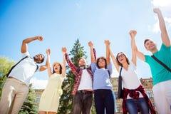 Tutti insieme! Punto di vista di angolo basso degli studenti felici con le armi alzate Immagini Stock