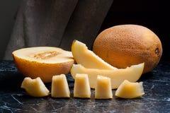 Tutto, metà e frutta affettata del melone di melata su backg di marmo scuro Fotografia Stock