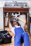 Tuttofare che ripara un lavandino con gli elevatori Immagini Stock