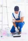 Tuttofare che utilizza il rullo di pittura nel vassoio a casa immagini stock