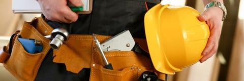 Tuttofare sconosciuto con le mani sulla cinghia dello strumento e della vita con gli strumenti della costruzione contro fondo gri fotografia stock
